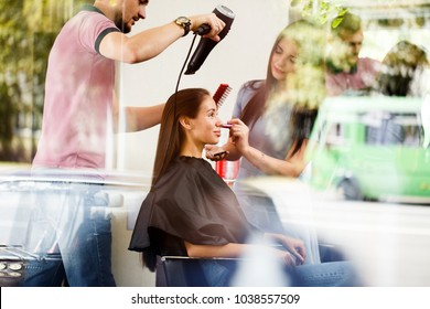 A young woman in a beauty salon with a hairdresser and a make-up artist. View through the window