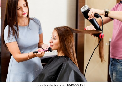 A young woman in a beauty salon with a hairdresser and make-up artist