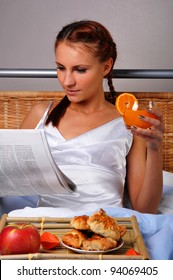 The young woman in bed at breakfast reads the newspaper