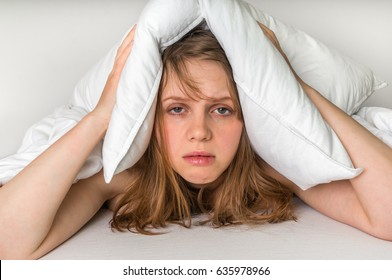 Young woman in bed covering ears with pillow because of noise