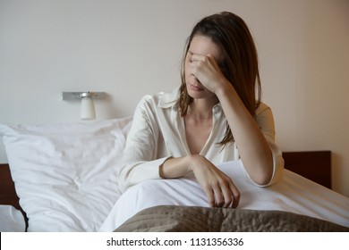 Young woman in the bed covering face with hand, depression, relationship difficulties, migraine or morning sickness concept