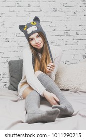 Young woman in bed in cozy bedroom in knitted cat hat. Matte filter, studio lighting