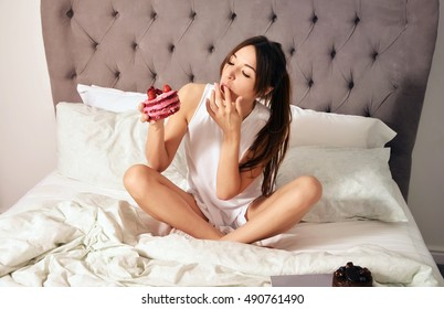 Young woman in bed eating a strawberry cake. Sexy girl in white nightie