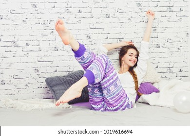 Young woman in bed relaxing and stretching, wearing her modern pajamas. Cheerful teenage girl in the morning.