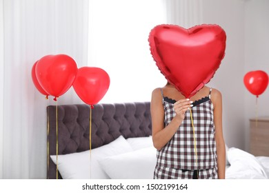 Young woman in bedroom decorated with air balloons. Celebration of Saint Valentine's Day
