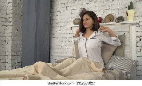 Young woman in bedroom in the morning. Happy smiling lady stretched just woke up. Adult brunette wearing in white classic sleepwear. Girl sitting on the bed at home.