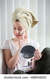young woman begins the cream on her face lotion, she wears a green towel