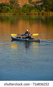 A young woman begins a trip around a lake in a kayak.