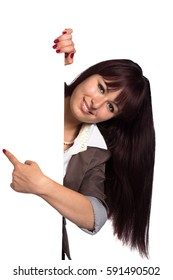 Young woman behind blank wall with copy space and pointing finger to something isolated on white background