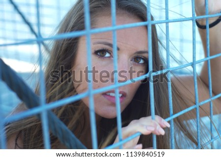 young woman behind metal fence grid jail locked