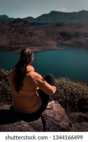 young woman from behind sitting in mountains of gran canaria with a stunning view across the island