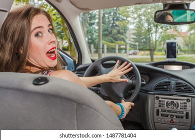 Young woman behind steering wheel. Confused, anxious female passing driver license exam, driving a car, being scared and stressed out.