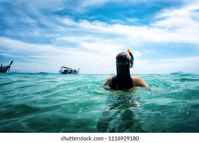 young woman from behind swims in the open sea while snorkeling with blue sky and clouds during summer trip
