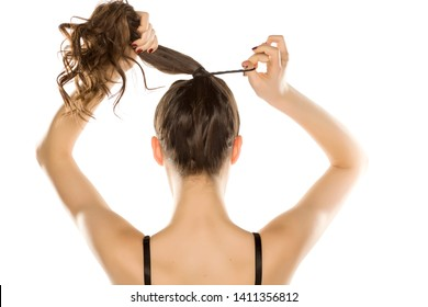 Young woman from behind,  tying her hair on white background