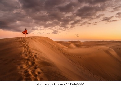 young woman from behind walking in sand dunes of maspalomas, gran canaria