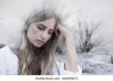 Young woman behind window glass on gray rainy day feeling sad