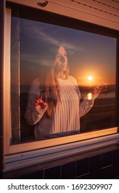 Young woman behind a window. You can see the reflection of a sunset over the sea on the glass.