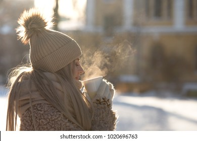 Young woman in beige fur coat, hat with pompon, scarf and white mittens holding steaming white cup of hot tea or coffee, outdoor in sunny winter day, side view/ Winter time concept/ Bask in the cold