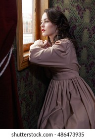 Young woman in beige vintage dress of early 20th century looking trough the  window in coupe of retro railway train
