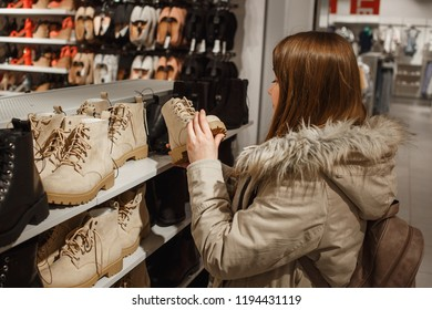 Young woman in beige winter clothes choosing trendy beige winter boots in the store.
