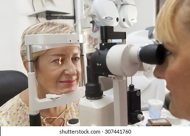 Young woman is being examined of her eyesight by optometrist