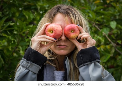 Young woman being silly holding apples to her eyes during family trip to pick apples at an apple farm