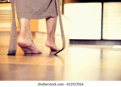young woman being walking on the tiled floor in bathroom