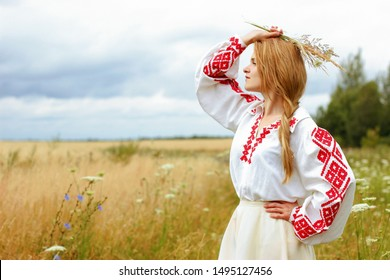 Young woman in a Belarusian folk traditional costume in a golden wheat field.