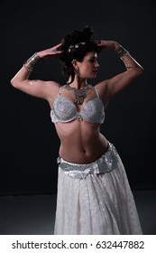 Young woman belly dancer in exotic dress with gems poses in studio
