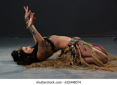 Young woman belly dancer in exotic dress with gold, dancing tribal fusion dance in studio.