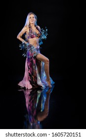 Young woman belly dancer in oriental multi-colored costume with feathers on a black background