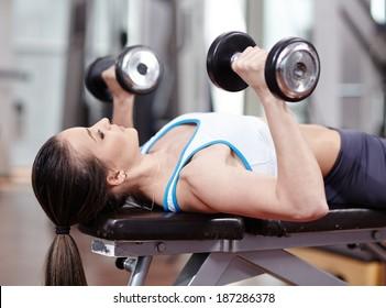 Jeune banc de femme pressant avec des haltères dans la salle de sport, travaillant des trompes et de la poitrine
