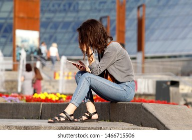 An young woman bent over and looks on a mobile phone sitting on a street in a sunny summer day,face covered with hair