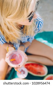 Young woman with berry smoothie outdoors