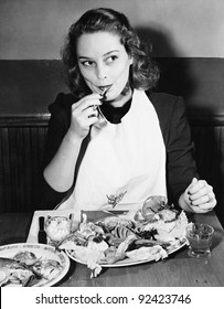 Young woman with a bib eating Lobster