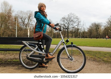 A young woman with a bicycle in the park