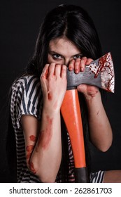 Young woman with a big bloody axe over black background