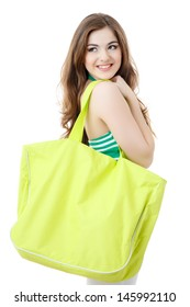 young woman with big green bag over her shoulder standing looking sideways isolated on white