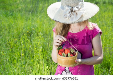 Young woman in the big hat are holding the bowl with strawberries in green field.
