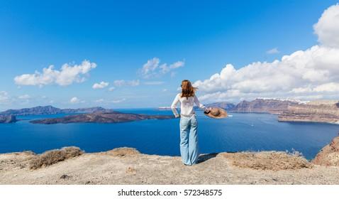 Young woman in big hat on the beach, Santorini island, Greece