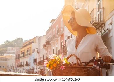 Junge Frau mit dem Fahrrad auf Ponza Island Hafen in Italien. Tourist mit großem Hut, Modehemd und buntem Rock. Korb mit Wein und Blumen vor den Geschäften und Booten.