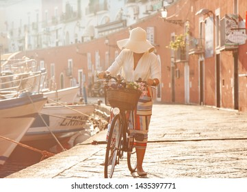 Young woman with bike at Ponza Island harbor pier in Italy. Tourist with large hat, fashion shirt and colorful skirt. Basket with wine and flowers in front of shops and boats. 11_Ponzabici_1048