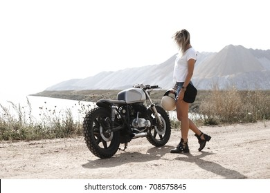 Young woman biker with custom cafe racer motorcycle parking on the road right side and sunset, sea background, nobody