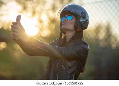 Young woman biker with helmet jacket and motorcycle glasses making a selfie smiling and sending a kiss with her happy mobile phone at sunset
