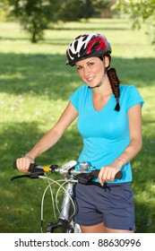 Young woman, biker with her bike