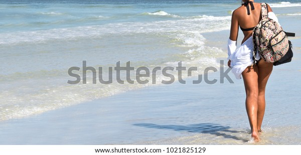 Young Woman in a Bikini with a backpack Walking on the Beach. Horizontal Banner with Copy Space