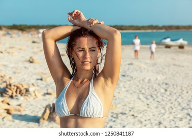 Young woman in bikini at the beach looking into the distance