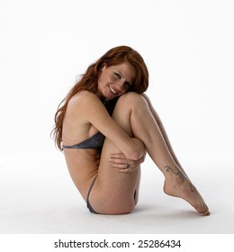 Young woman in bikini crouched on a white background