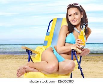 Young woman in bikini drink juice through a straw on beach.