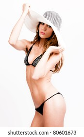 young woman in bikini and hat, studio shot